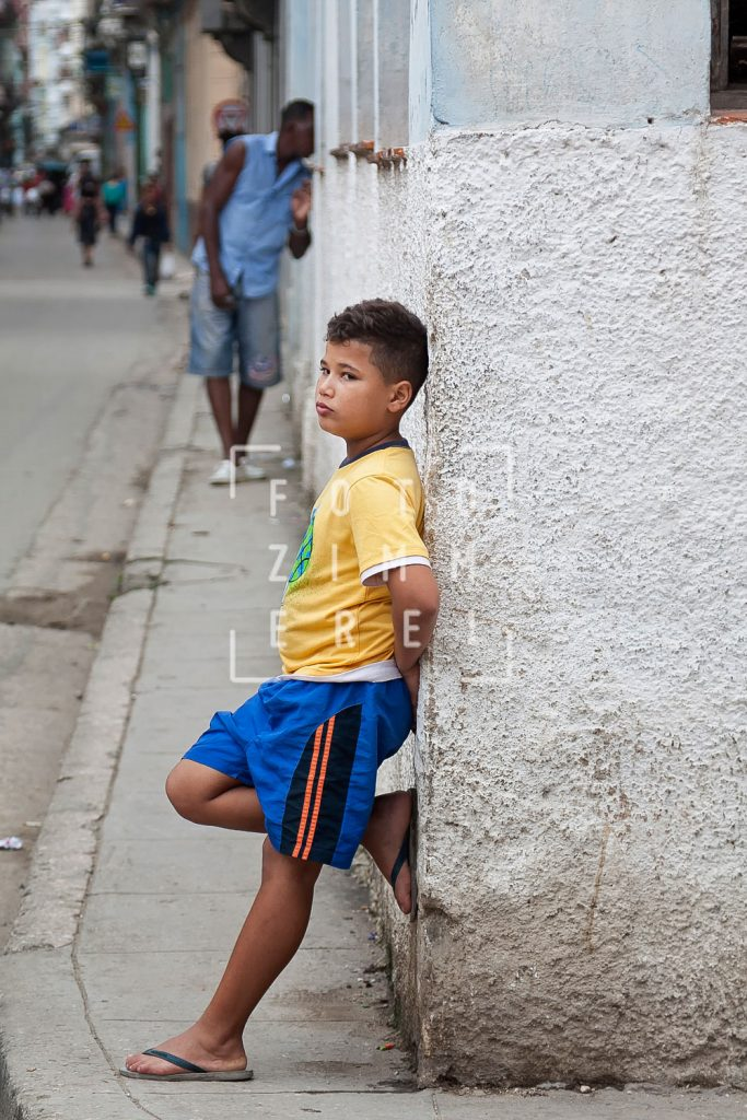 boy leaning back at a wall in the street of havannain havanna